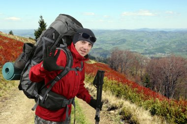 Happy traveler equipped with a red jacket on the hillside raised