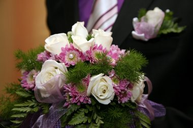 beautiful wedding bouquet of white roses in the hand of the groom