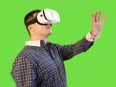 Man by Green Screen with Hand Extended Wearing VR 360 Glasses