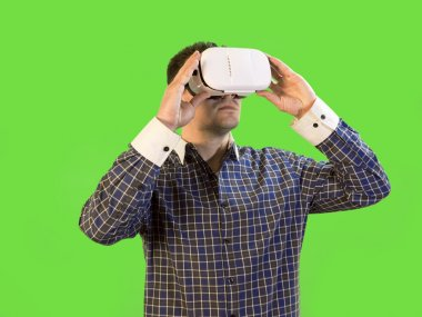 Man by Green Screen Holds Virtual Reality Headset to His Eyes