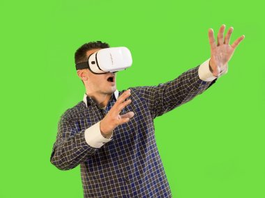 Man by Green Screen with Hands Out in Shock Wearing 360 Virtual Reality Set