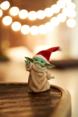 Dec, 2020: Display of Baby Yoda, an action figures, standing in a red cap on christmas background. Bokeh effect. High quality photo stock vector
