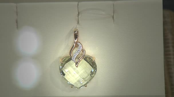 Golden pendant with diamond in a heart shape.