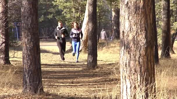 Boy and girl running on a forest path.