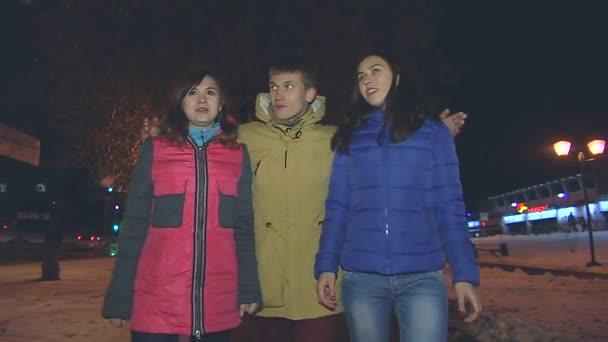 Chlápek a dvě dívky procházejí uličkou. On je objetí