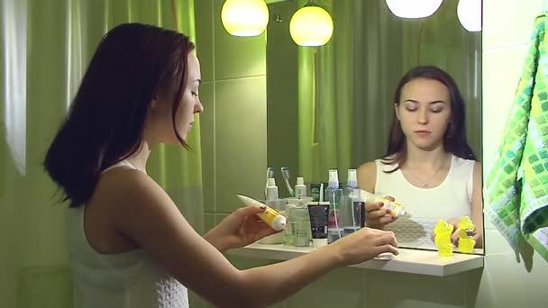 Fiatal lány helyezze a krémet az arc. 2 lövés