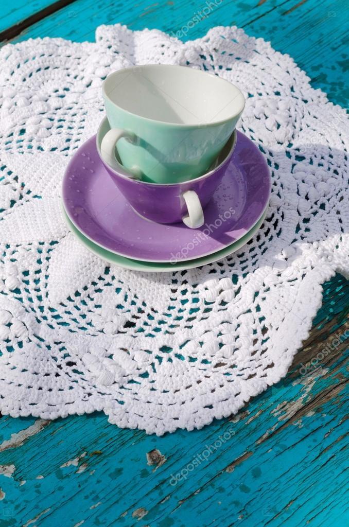 Porzellan Teetassen-Set auf eine weiße gehäkelte Serviette ...