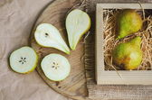 Ripe and juicy pears on background of packing paper, canvas burlap and wooden board, toned and faded