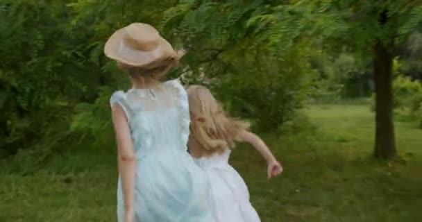 Glückliche kleine Mädchen laufen durch Waldpark Glückliches Kind zahlt im Garten Kinder