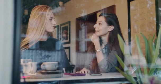 two pretty girls relaxing and have conversation and drink coffee in cafe