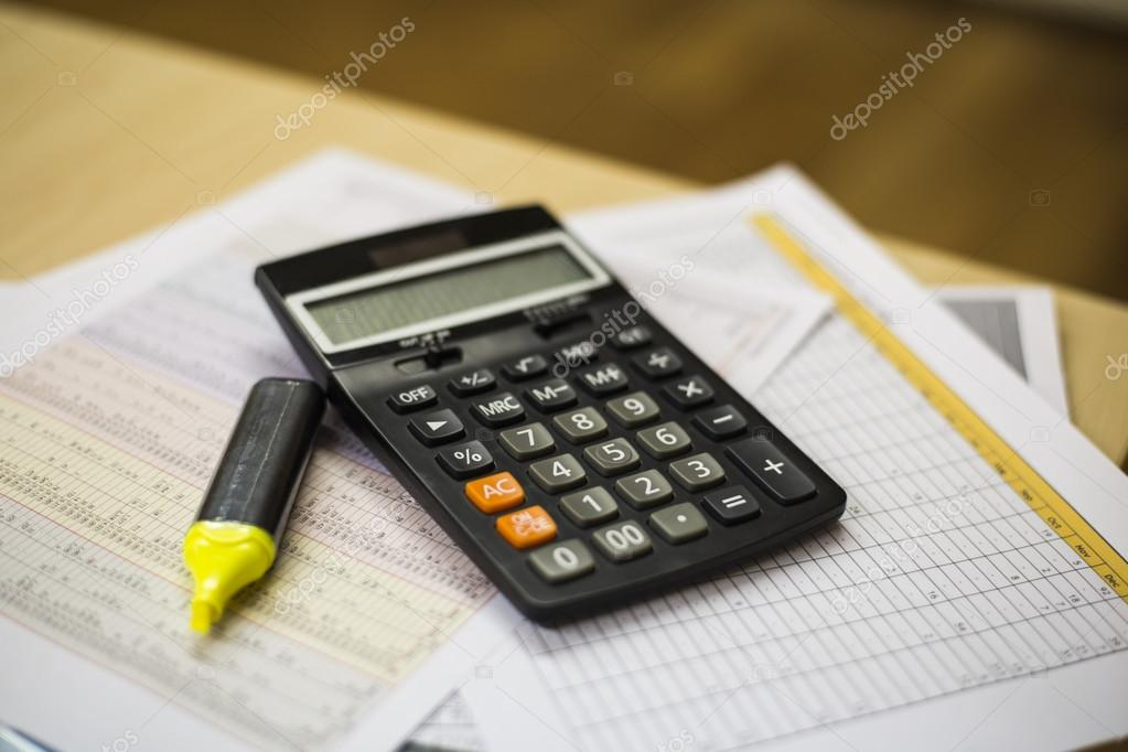 calculator on sales report charts stock photo tapanuth 115795546