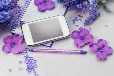 Office supplies business women. Still life. Phone notebook and pen. Some office stuff on a white background. Accessories on the table. Purple color objects