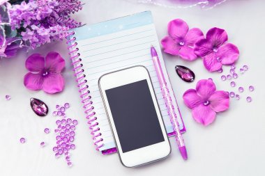 Office supplies business women. Phone, notebook and pen. Some office stuff on a white background. Accessories on the table. Purple pink color interior details.