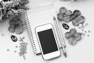 Phone, notebook and pen. Some office stuff on a white background. Accessories on a desk. Black and white color interior details.