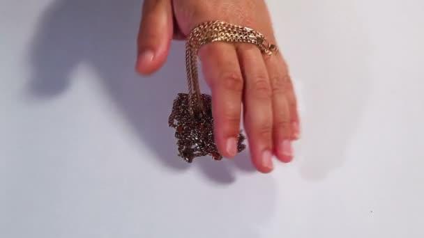 Zlatý řetízek v ruce na bílém pozadí