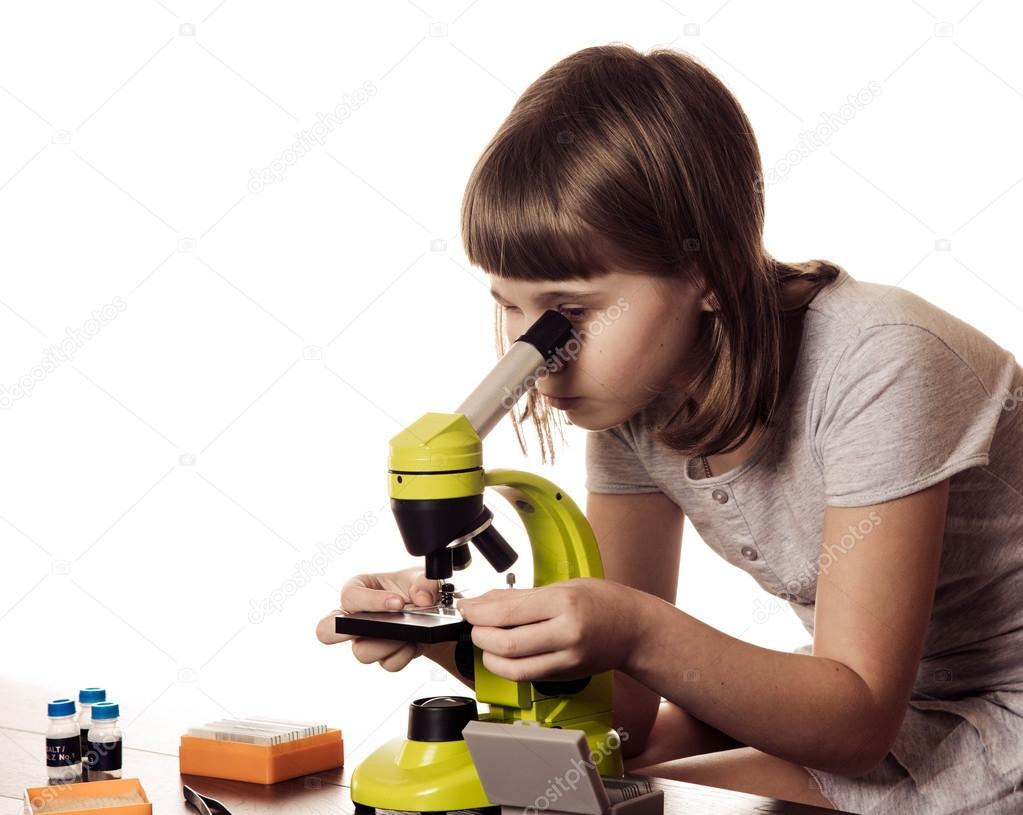 Kleines mädchen studieren mit mikroskop auf weißem hintergrund