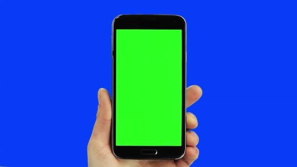 Fekete szúró telefon chroma key kék és zöld valódi kézzel