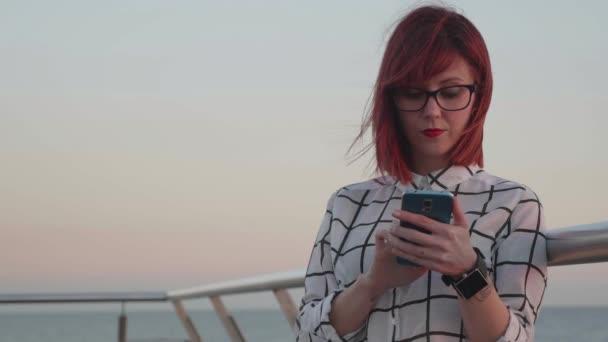 A szemüveg a part menti környezet használ egy okos telefon, naplemente alatt nő