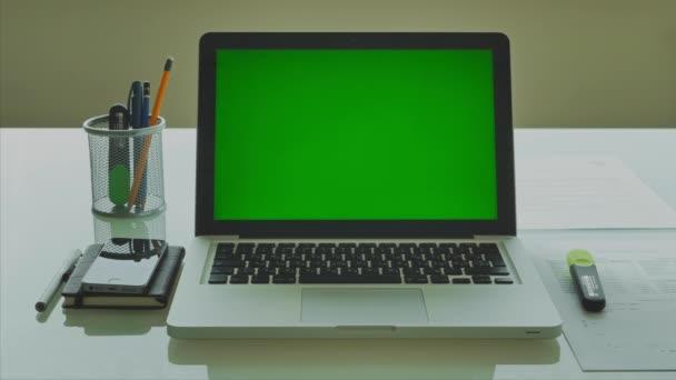 Laptop-val zöld képernyő (Chroma-key), a modern üveg asztal 4k hivatalban
