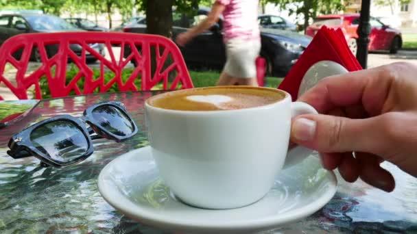 Žena pít šálek cappuccina. Brýle jsou v blízkosti pohár