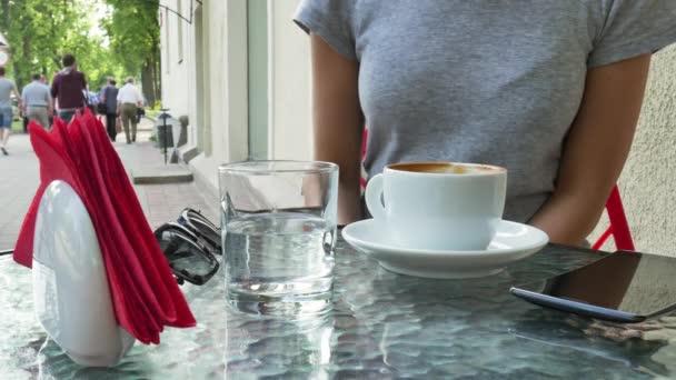 Nő a kávézóban kávét iszik, az utca