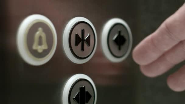 Muž tlačí na tlačítko otevírání dveří výtahu