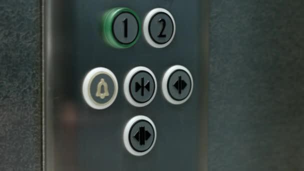 Muž tlačí na tlačítko Zavřít dveře výtahu. Zblízka