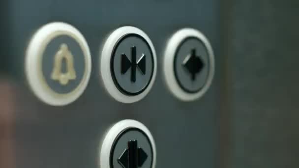 Muž tlačí na tlačítko otevírání dveří výtahu. Zblízka