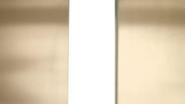 Zlaté kovové výtahové dveře otevřené na světlo