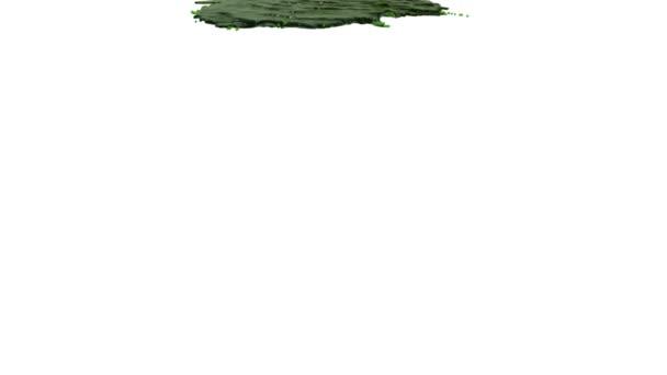 grüne Flüssigkeit ergießt sich in Zeitlupe auf weiß