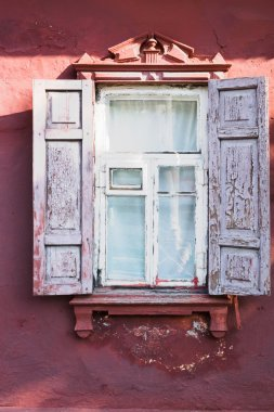 Old decrepit wooden window with exterior shutters and decor