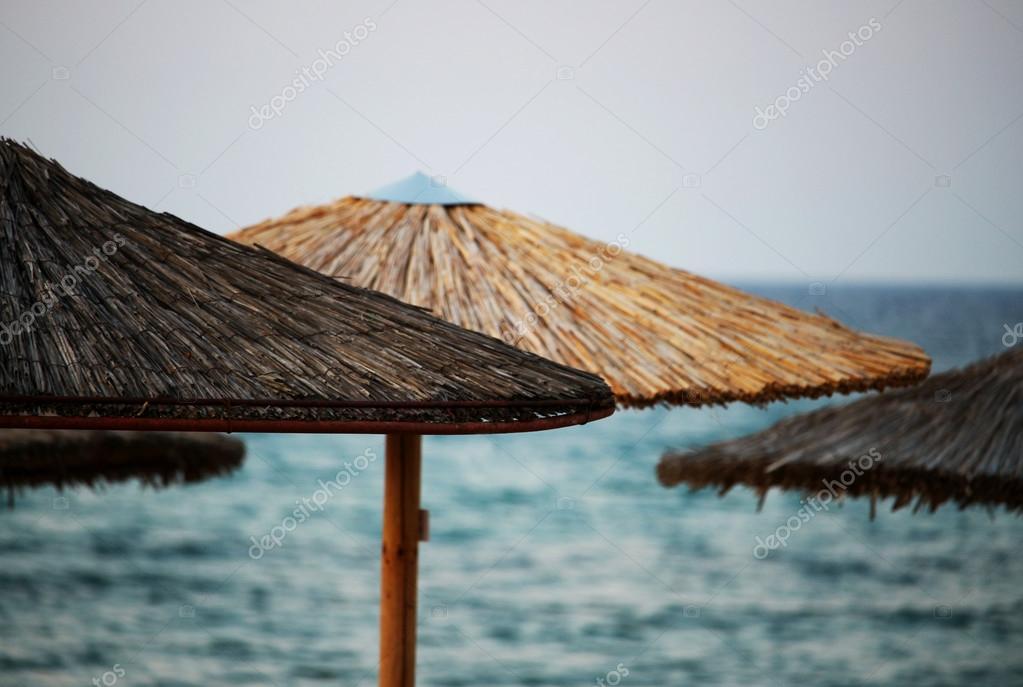Houten zon parasols op het strand door zee stockfoto dalaxey 82507476 - Zon parasol ...