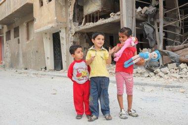 Children play near damaged houses