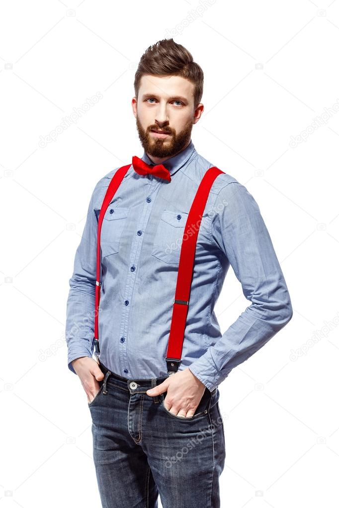 ded2772e6f7f Stylish guy wearing blue shirt, red bowtie and suspenders isolated on  white. smile. stand. hands in the pocket. — Photo by zamuruev