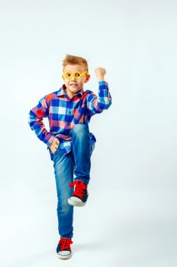 Little boy wearing colorful plaid shirt, blue jeans, gumshoes, plastic glasses having fun in the studio