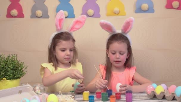 Frohe Ostern. Zwei Schwestern bemalen Ostereier. Glückliche Familienkinder bereiten sich auf Ostern vor. Niedliches kleines Mädchen mit Hasenohren am Ostertag