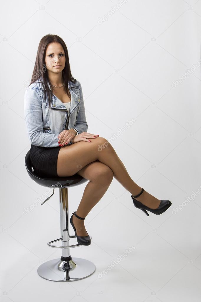 Девушка сидит на барном стуле