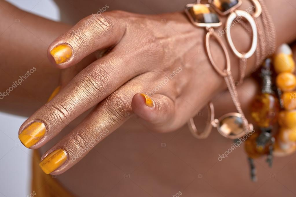 Accessories On Womans Heands In Golden Yellow Colors Nails Stock