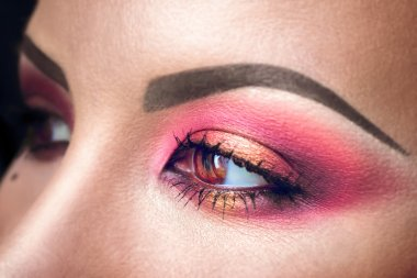 Elegance close-up of female eye with pink and gold eyeshadow. Macro shot of beautiful womans face part. Wellness, cosmetics and make-up.