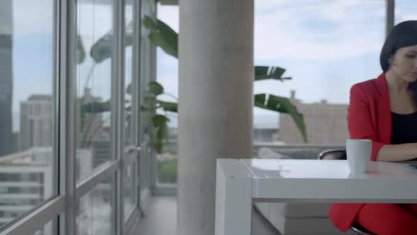 Usmívající se mladá podnikatelka recepční nosit bezdrátové sluchátka videokonference pracuje na notebooku.