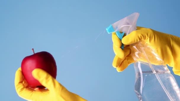 Handschuh-Hände sprühen wegen Covid-19-Pandemie Desinfektionsflüssigkeit auf Apfel