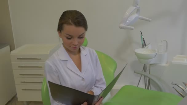 Dantist is Reading a Notes in a Fold Smiling Raises Head Girl in Lab Coat is Smiling Sitting on a Chair at Dental Treatment Room Young Pretty Doctor Woman