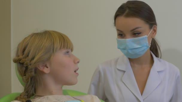 Zahnarzt behandelt Mädchenzähne mit Zahnlampenpatient junges blondes Mädchen sitzt am Stuhl Arzt trägt Schutzbrille und Laborkittel