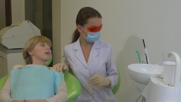 Zahnarzt mit Brille benutzt eine Zahnlampe Patientin junge blonde Mädchen Kind sitzt auf dem Stuhl Arzt ist Maske Labormantel spricht mit einem Mädchen Zahnklinik