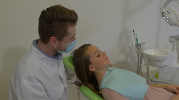 Dentist is Sitting Behind a Clients Head Talking Man in Mask is Examining a Teeth of a Patient Woman With Napkin on Her Chest Dental Clinic Visit