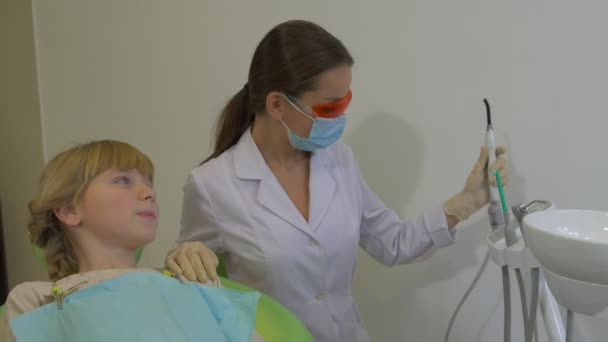 Dentist is Using a Dental Lamp Treating a Teeth Patient Girl Doctor in  Glasses and Mask With uv Lamp Patient at Dental Treatment Room Visit to the  Dentist