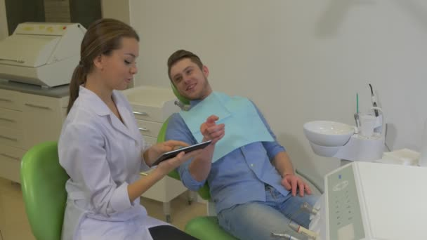 Dentist Clicks a Tablet Shows to a Patient Client is Smiling Pointing on a Tablet Choosing Something Dental Clinic Young Female Doctor Male Client