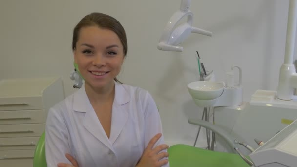 Friendly Dentist Young Woman Sitting Crossed Arms Lab Coat Girl is Smiling Looking at Camera Dentists Machine Dental Lamp Green Chair Dental Clinic