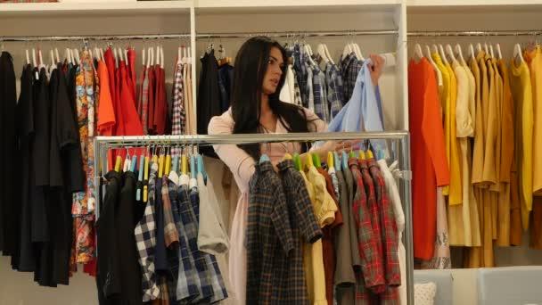 Žena je volba šaty vezme tričko nabídky Shop klienta bruneta žena je nákup oblečení v Boutique oděvy jsou zavěšené na Trempels
