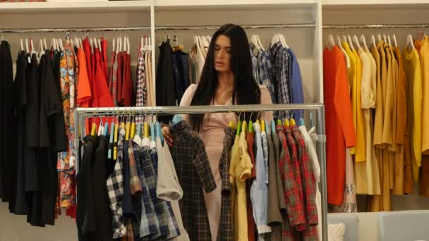 Žena je volba oblečení má šaty nabídky Shop klienta bruneta žena je nákup oblečení v Boutique oděvy jsou zavěšené na Trempels
